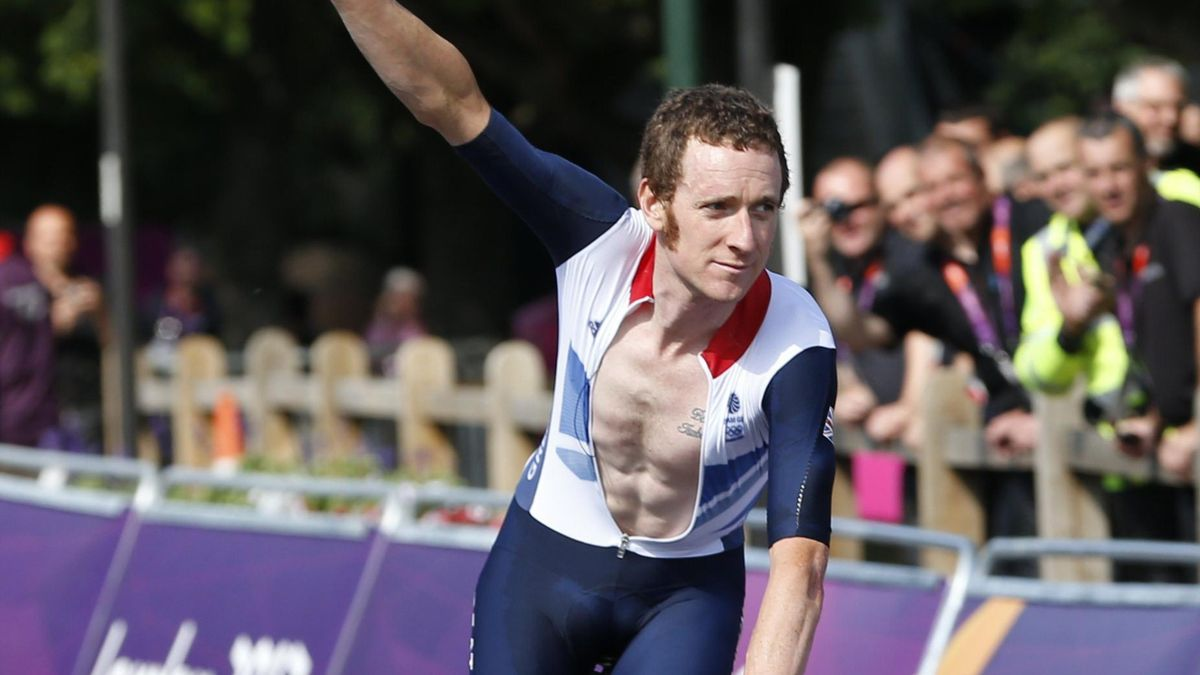 Britain's Bradley Wiggins raises his hand as he takes a victory lap after winning the men's cycling individual time trial at the London 2012 Olympic Games (Reuters)