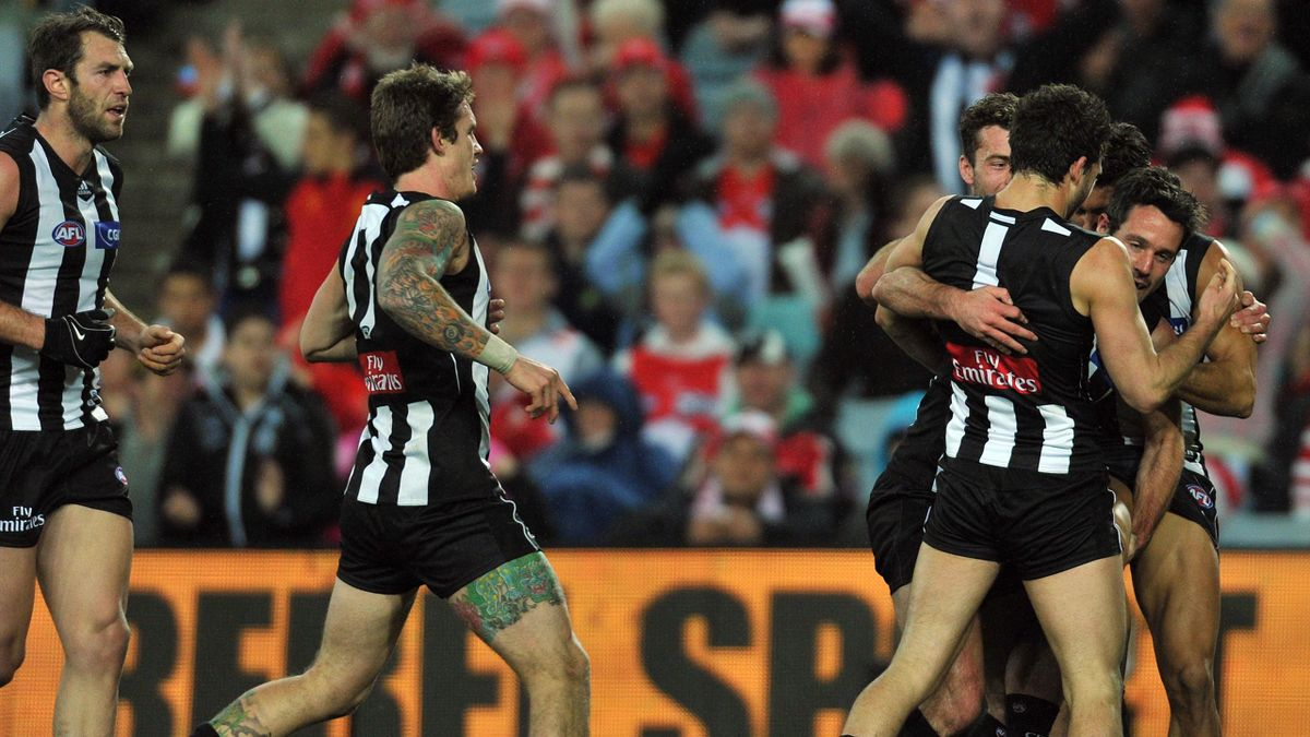 The Collingwood Magpies' players congratulate Alan Didak (right) after he kicked a goal (AAP/AUSTRALIA ONLY)