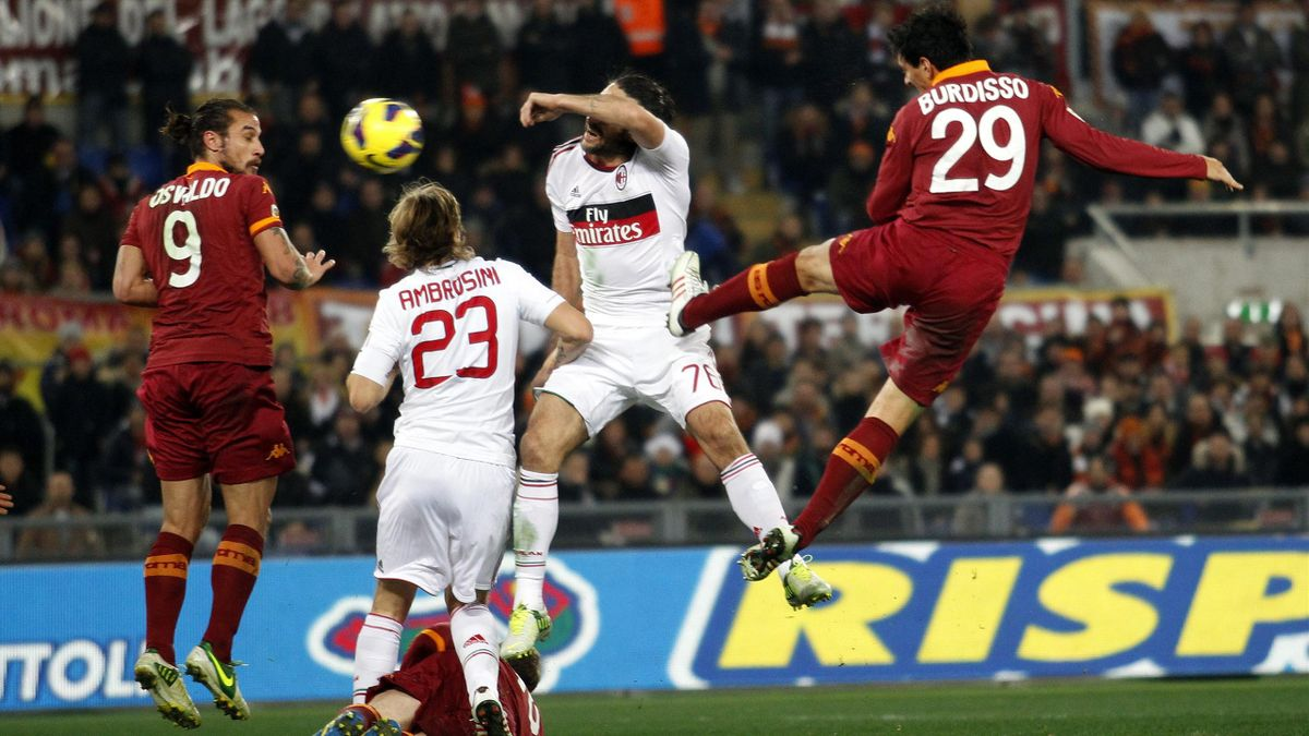 AS Roma's Nicolas Burdisso (R) heads the ball to score against AC Milan during their Italian Serie A soccer match at the Olympic stadium in Rome December 22, 2012 (Reuters)