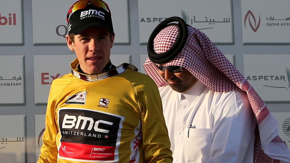 BMC Racing Team's Brent Bookwalter of the US (L) wears the leader's gold jersey after winning stage one of the 2013 Tour of Qatar