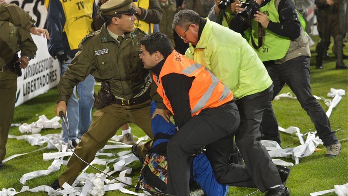 Police arrest fans during a fight on the field between Gremio and Huachipato players at the end of their Copa Libertadores match in Talcahuano (AFP)