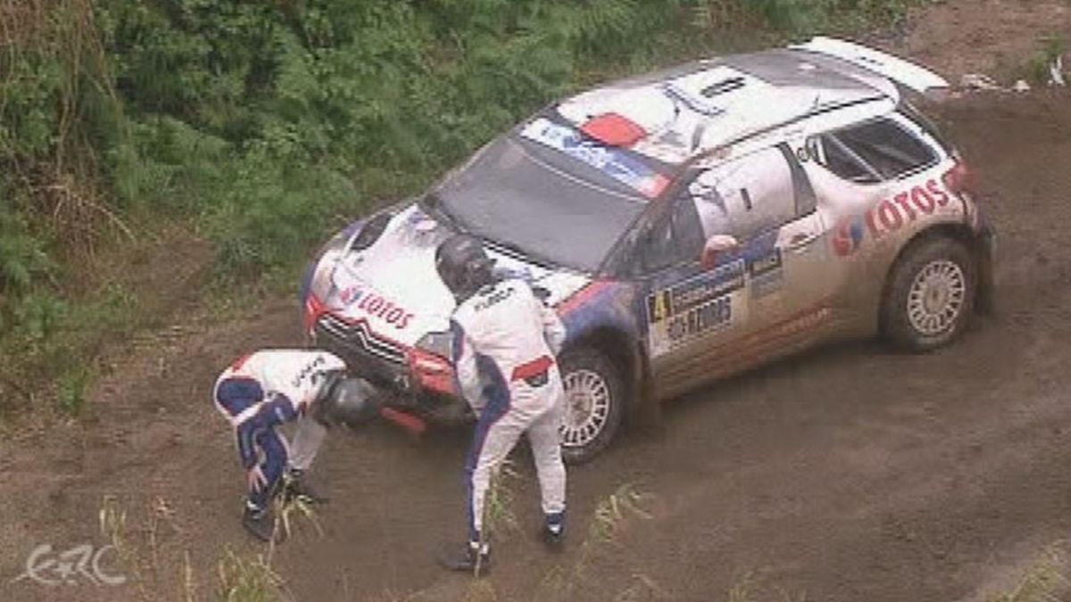 Robert Kubica looking at his car just after the crash