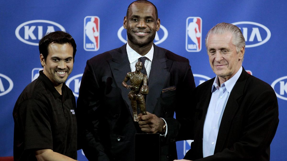 Miami Heat forward LeBron James (C) holds the trophy as he stands with head coach Erik Spoelstra (L) and team president Pat Riley (Reuters)