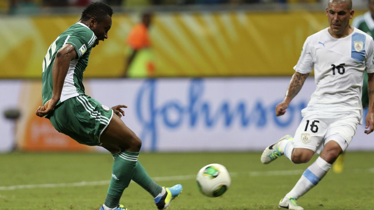 Nigeria's John Obi Mikel (L) scores a goal near Uruguay's Maximiliano Pereira during their Confederations Cup Group B match at the Arena Fonte Nova in Salvador June 20, 2013.