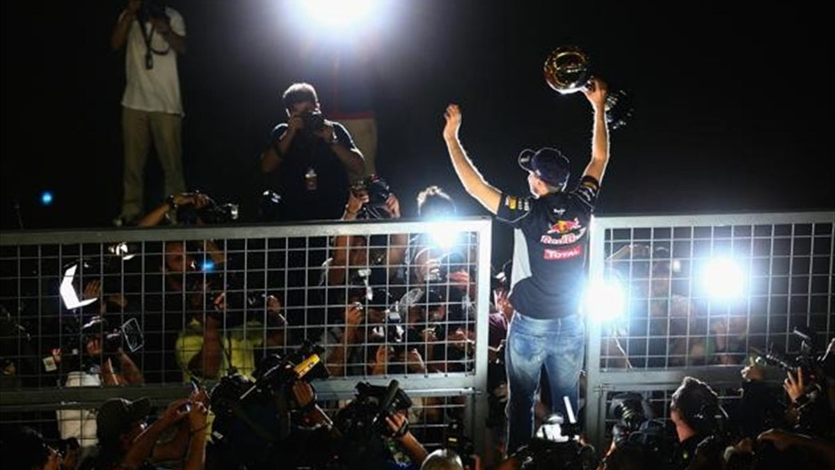 Sebastian Vettel of Germany and Infiniti Red Bull Racing celebrates with team mates in the pitlane after winning the Japanese Formula One Grand Prix at Suzuka Circuit on October 13, 2013 in Suzuka, Japan.