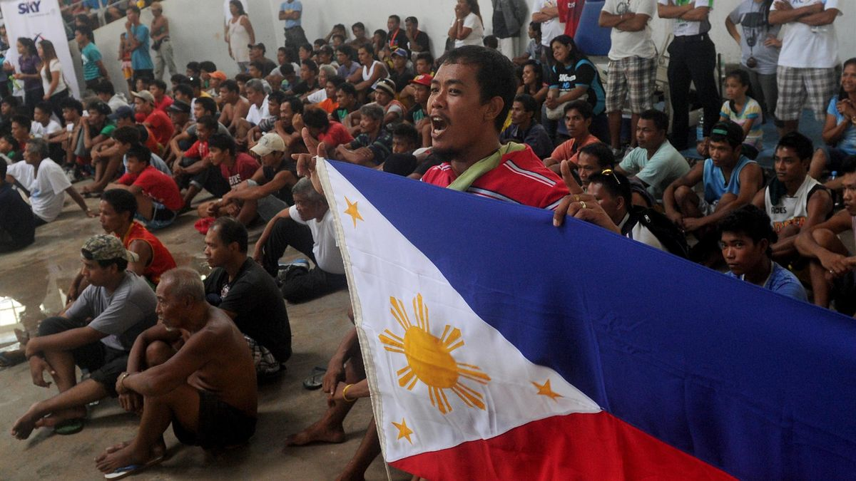 Typhoon survivors cheer as they watch the boxing match between Philippine boxing hero Manny Pacquiao