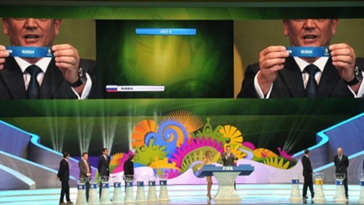 FIFA Secretary General Jerome Valcke (C and on screen) shows the name of Russia during the final draw of the groups for the Brazil 2014 FIFA World Cup, in Costa do Sauipe, Bahia state, Brazil, on December 6, 2013. AFP - Россия жеребьевка ЧМ 2014