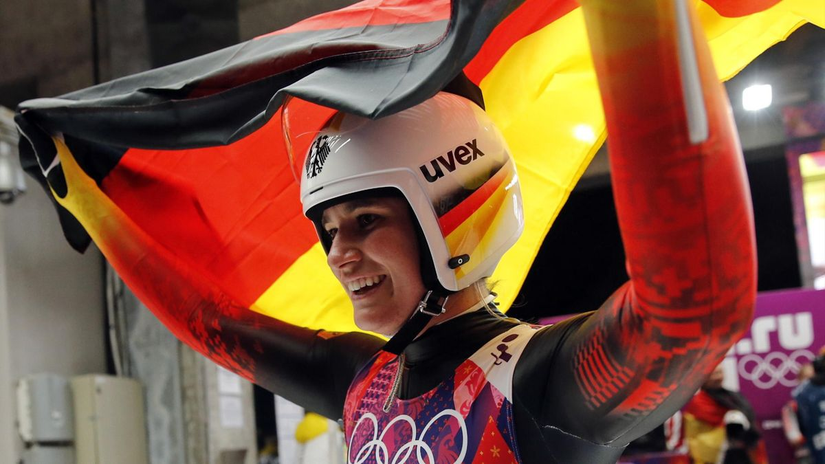 Germany's Natalie Geisenberger celebrates with a national flag after winning the women's luge singles (Reuters)