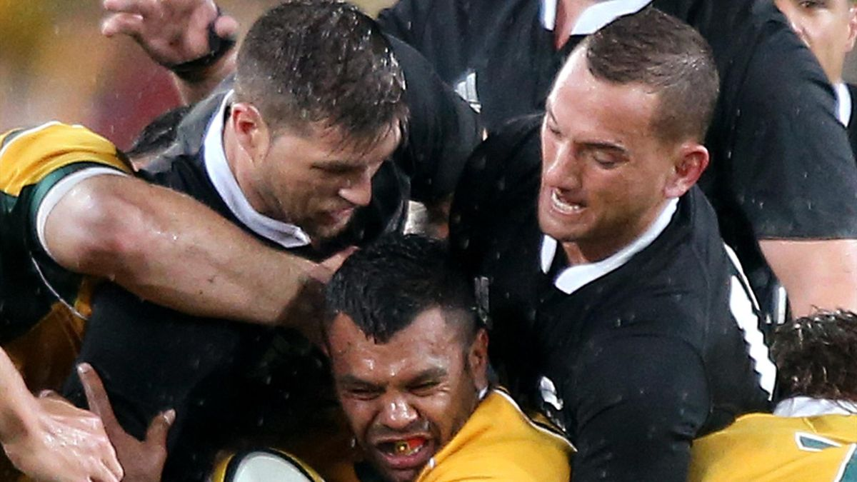 Australia's Kurtley Beale, center, is wrapped up by the New Zealand defense during their Bledisloe Cup rugby union test match in Sydney, Saturday, Aug. 16, 2014. (AP Photo/Rick Rycroft)