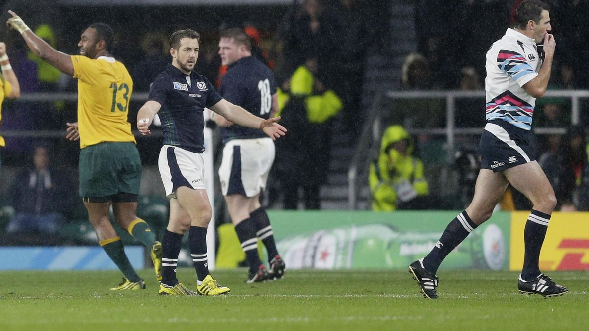 On the run: Referee Craig Joubert (R) leaves the field at the end of the game as Greg Laidlaw of Scotland looks on.
