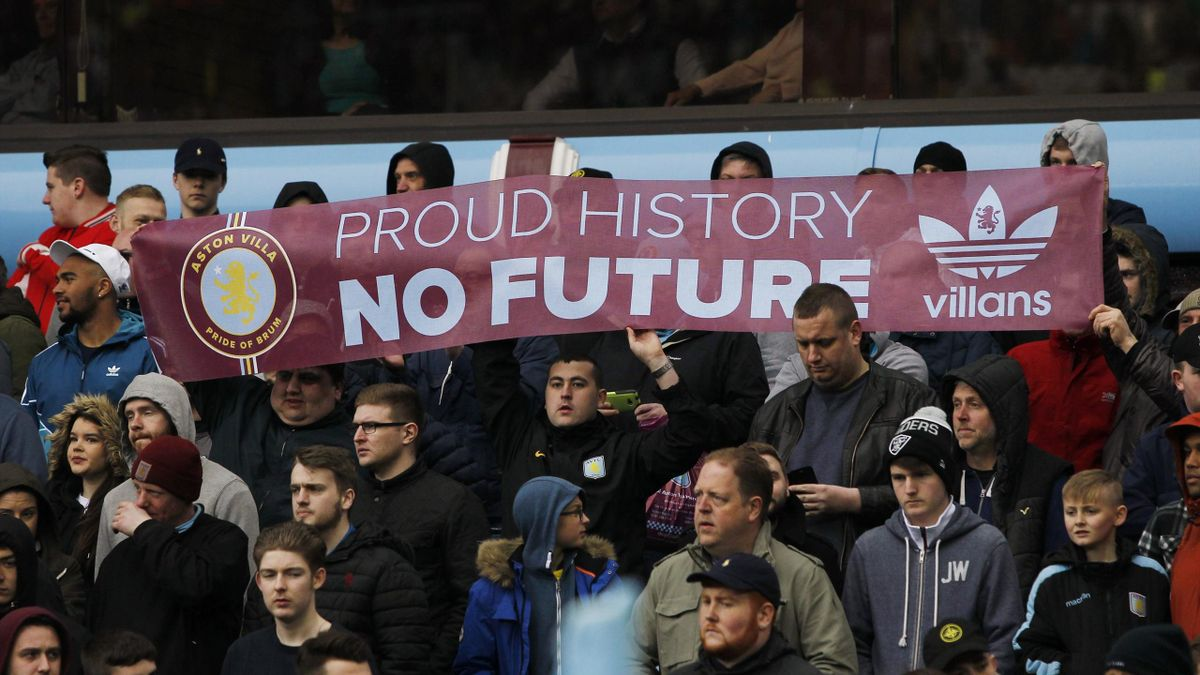 Aston Villa fans hold up a banner in protest.