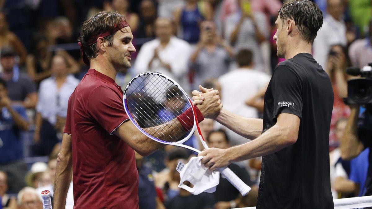 Roger Federer, left, and John Millman shake hands after the Australian's stunning win