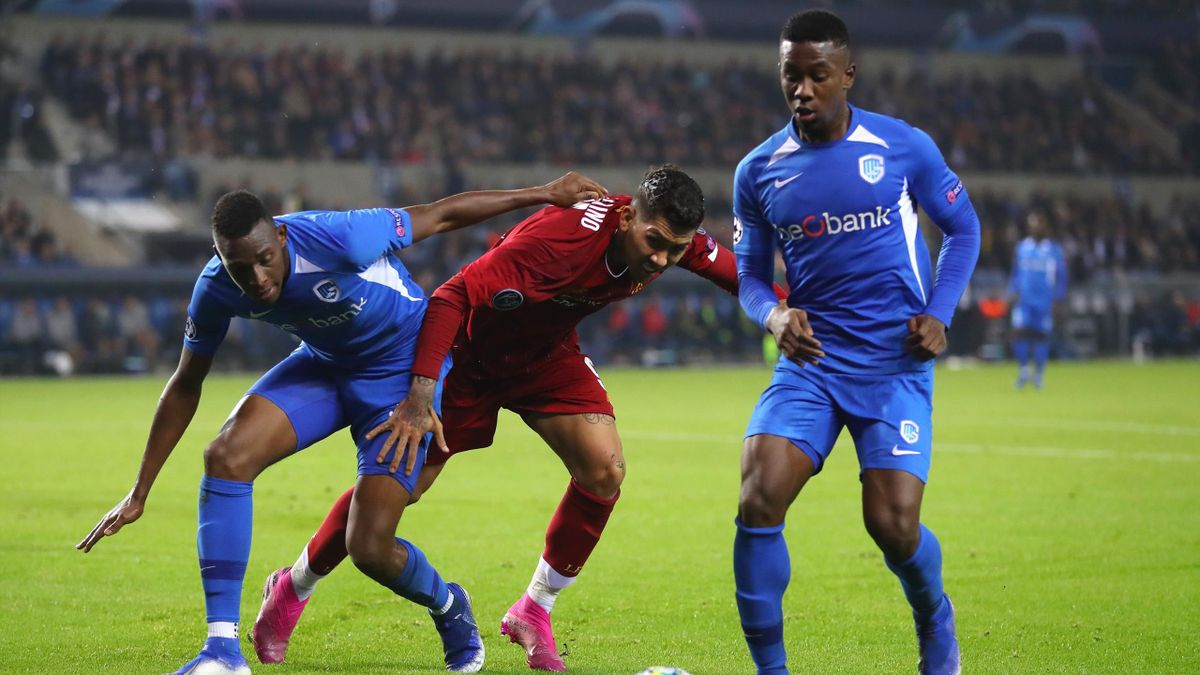 : Roberto Firmino of Liverpool is challenged by Jhon Lucumi of KRC Genk and Carlos Cuesta of KRC Genk during the UEFA Champions League group E match between KRC Genk and Liverpool FC at Luminus Arena on October 23, 2019
