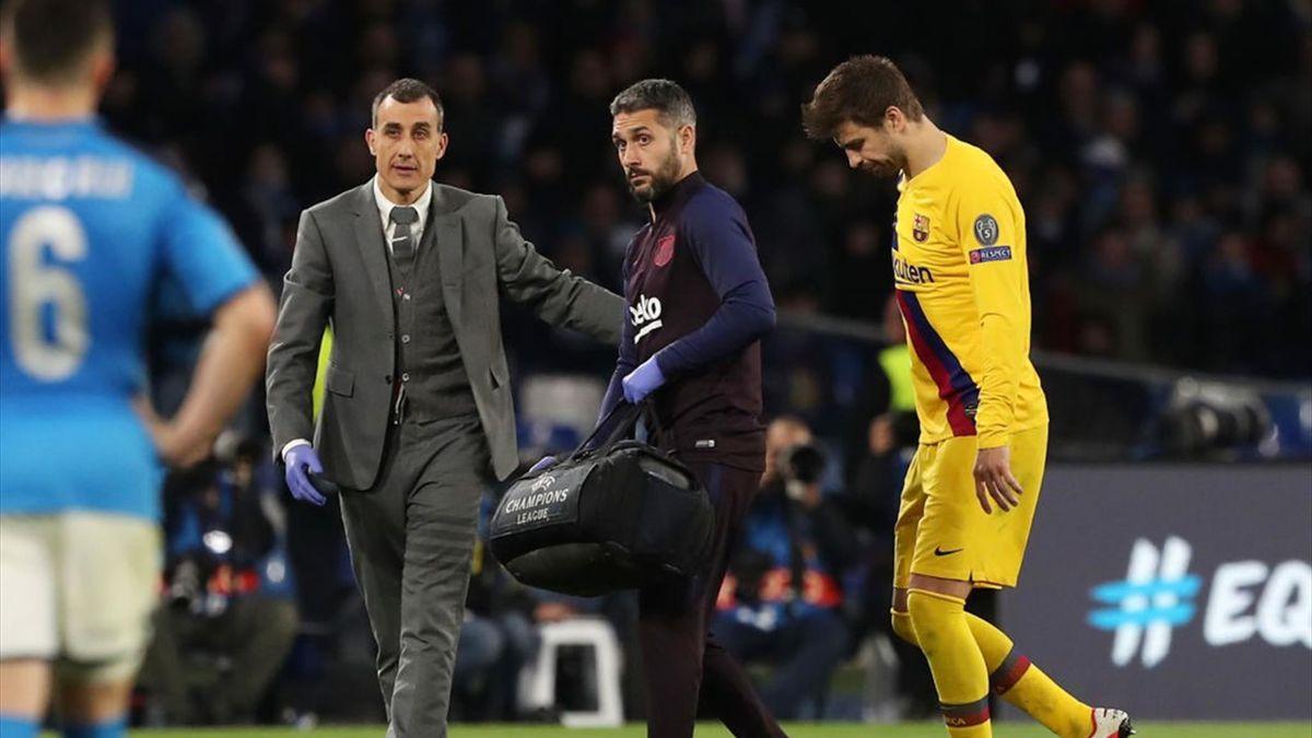 Piqué siendo atendido tras sufrir una lesión de tobillo en el Nápoles-Barcelon