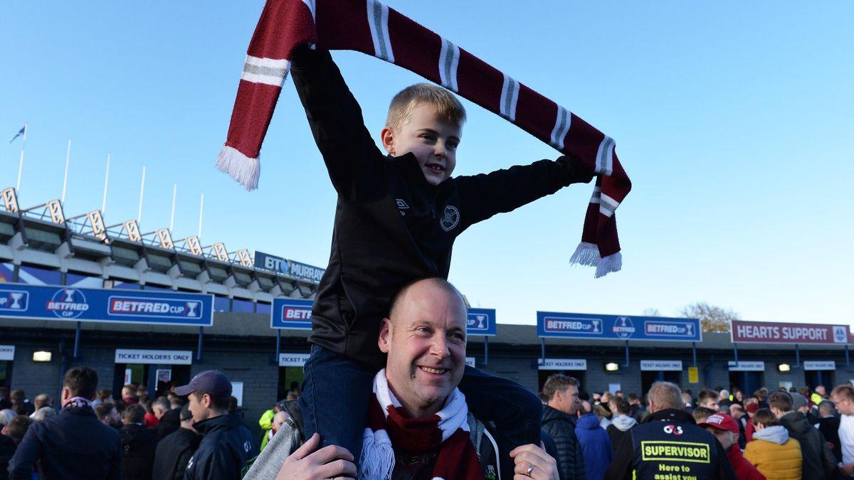 Doi fani, tată și fiu, merg la un meci de fotbal din Scoția