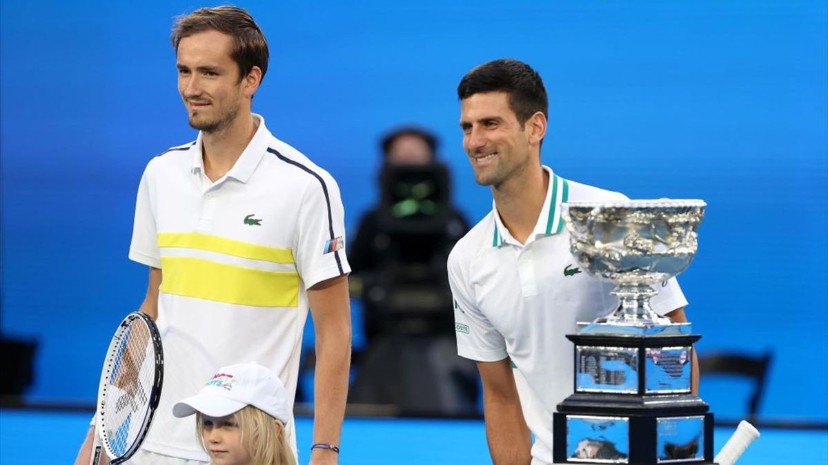 Serbia's Novak Djokovic (R) and Russia's Daniil Medvedev pose for pictures prior to their men's singles final match on day fourteen of the Australian Open tennis tournament in Melbourne on February 21, 2021. (Photo by David Gray / AFP) / -- IMAGE RESTRICT