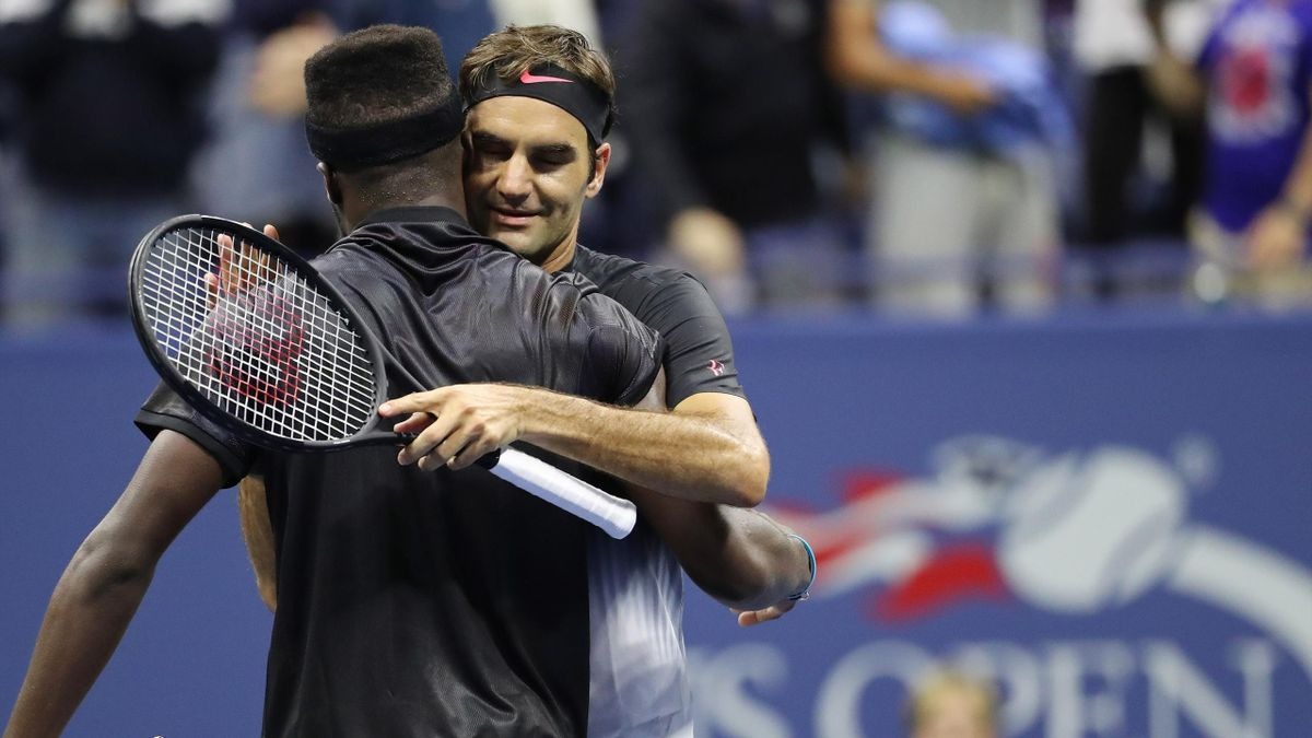 Roger Federer of Switzerland (R) hugs Frances Tiafoe of the United States (L) after their match on day two of the U.S. Open tennis tournament at USTA Billie Jean King National Tennis Center.
