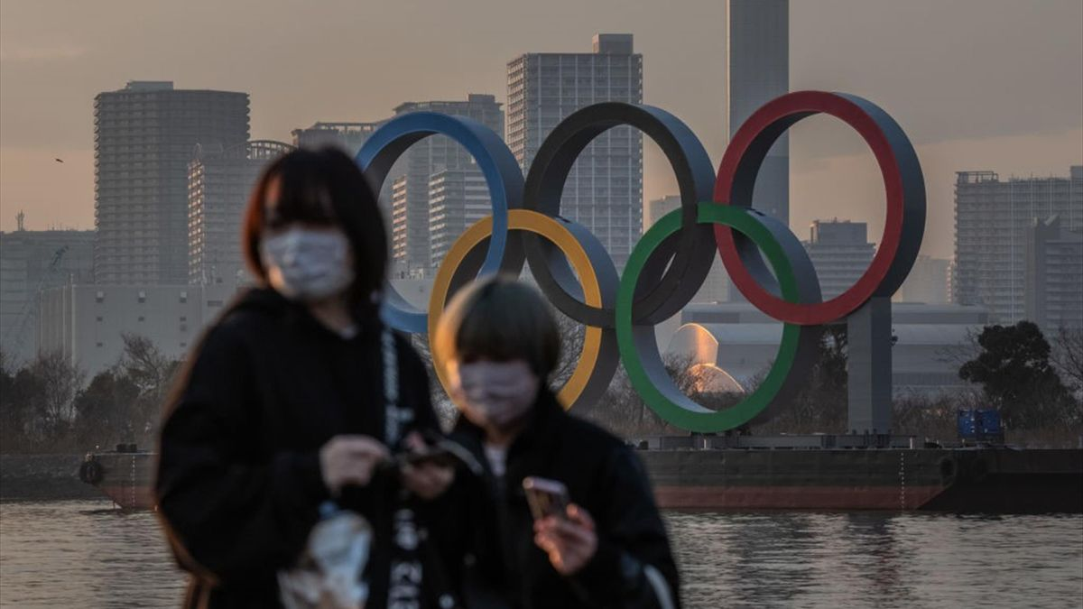 Women wearing face masks pass near the Olympic Rings on January 22, 2021 in Tokyo, Japan