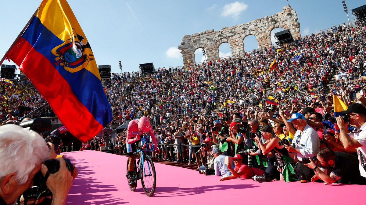 A fan waves the flag of Ecuador (L) as overall race winner Team Movistar rider Ecuador's Richard Carapaz reacts as he enters the arena after competing in stage twenty-one, the final stage of the 102nd Giro d'Italia - Tour of Italy - cycle race