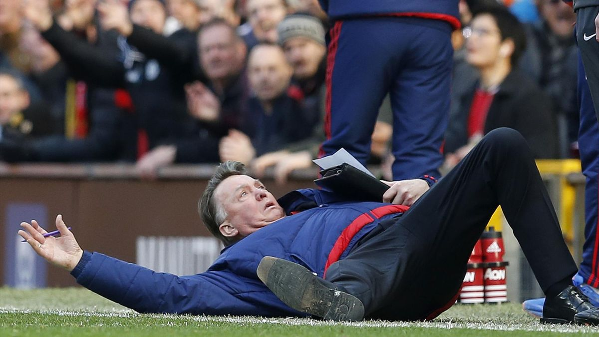 Manchester United manager Louis van Gaal lies on the side of the pitch to demonstrate a foul to the fourth official Mike Dean