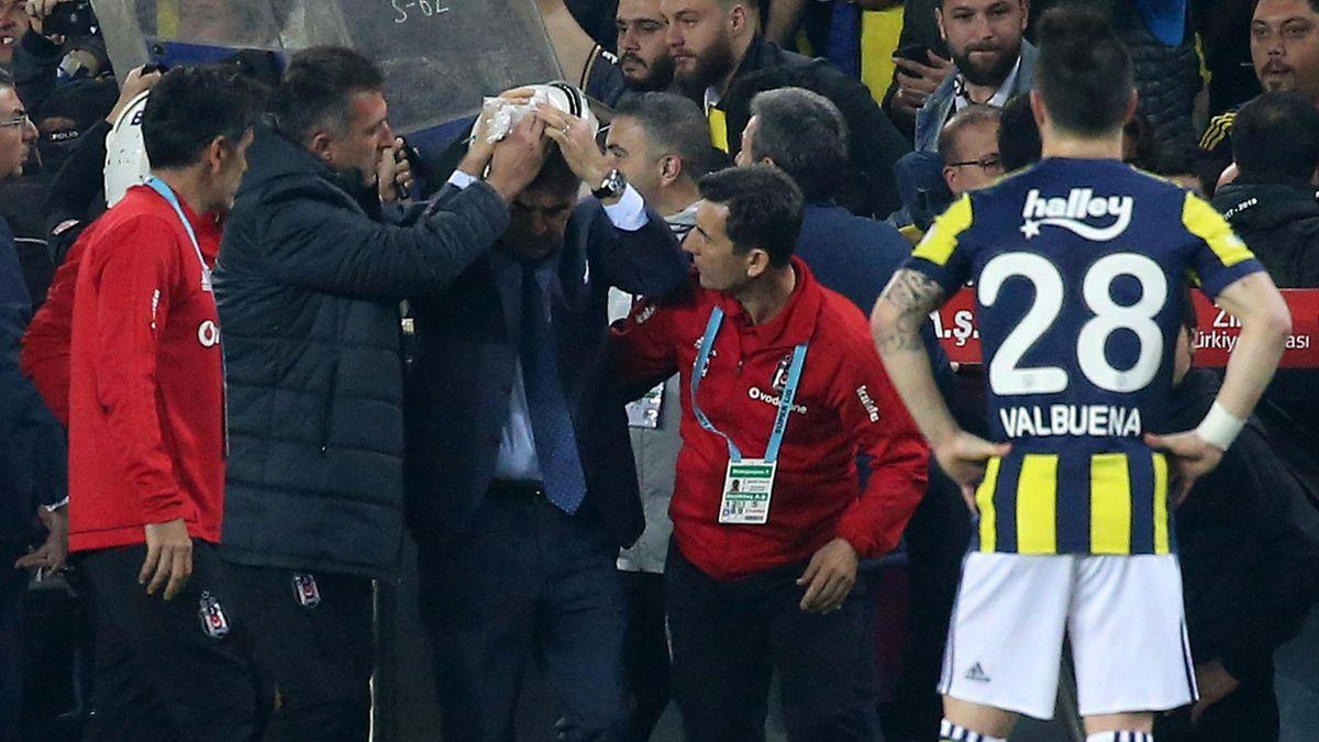 Besiktas head coach Senol Gunes (C) holds his head after being hit by an object