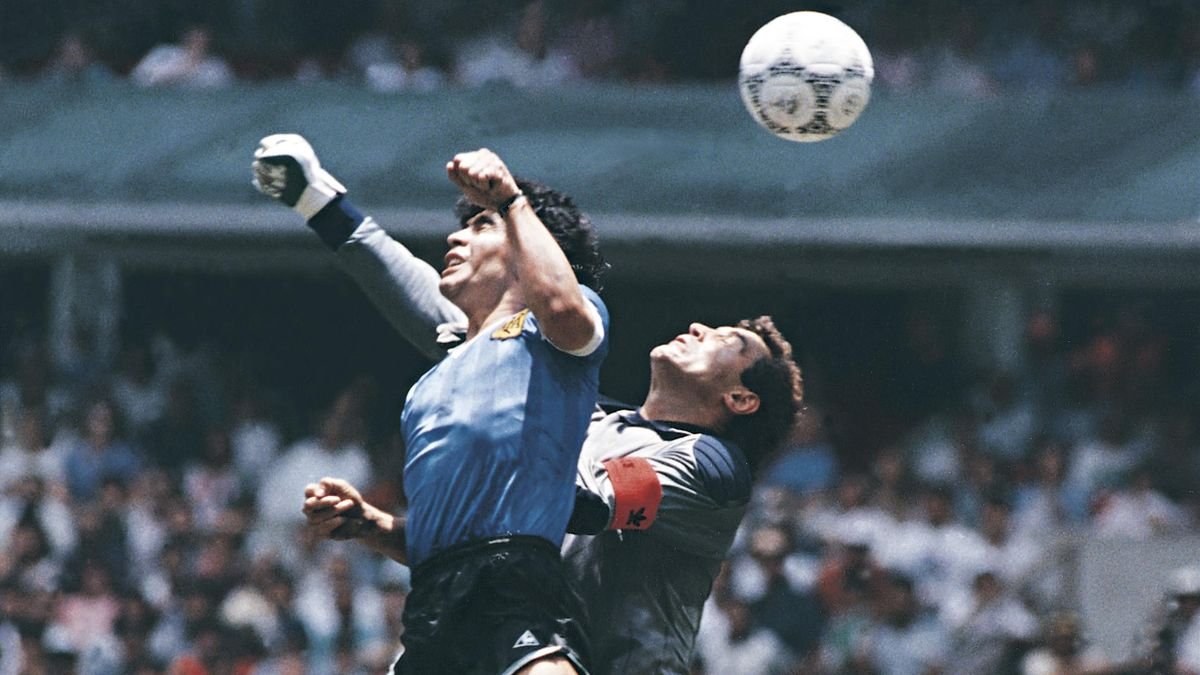 Diego Maradona of Argentina uses his hand to score the first goal of his team during a 1986 FIFA World Cup Quarter Final match between Argentina and England