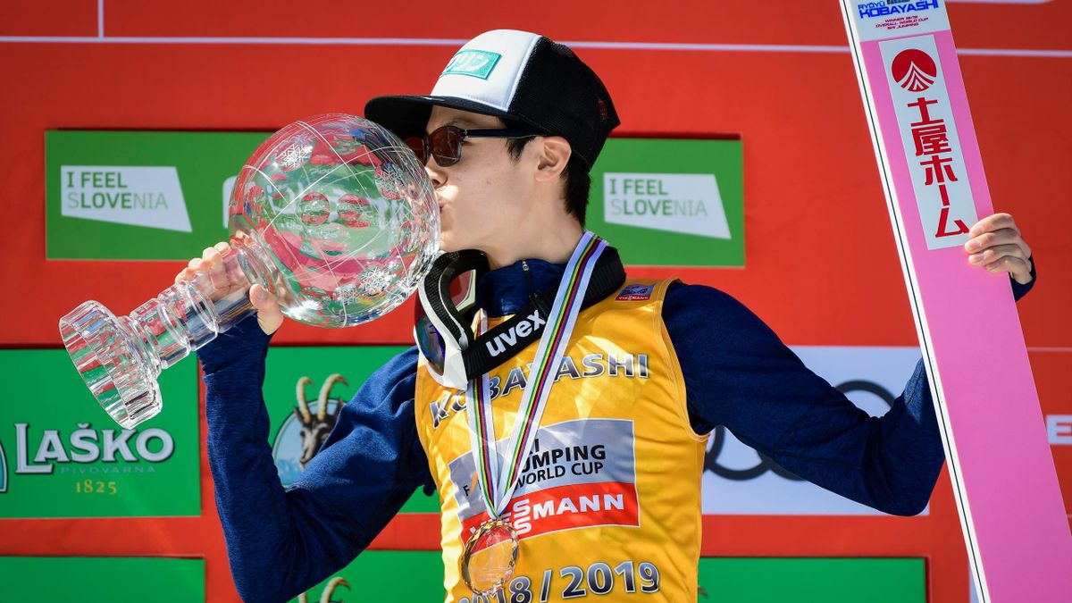 Japan's Ryoyu Kobayashi kisses with the crystal globe trophy after winning the overall classification of the FIS Ski Jumping World Cup in Planica, on March 24, 2019
