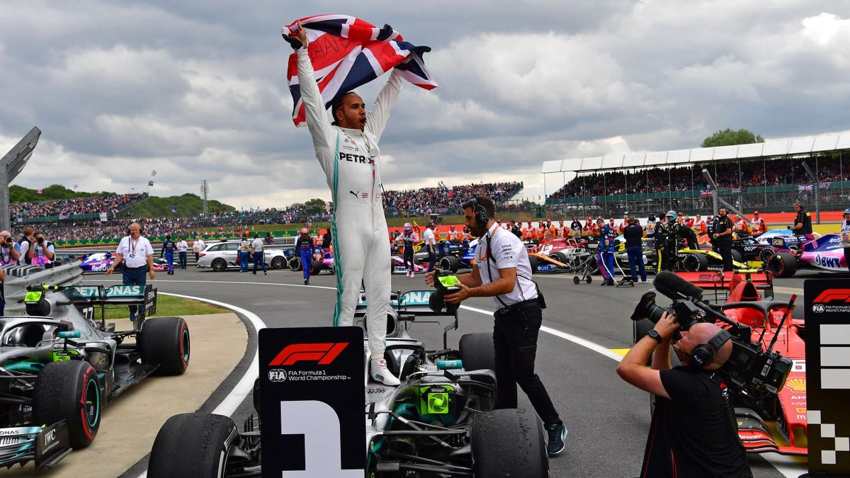 Mercedes' British driver Lewis Hamilton (C) waves the Union flag as he celebrates in parc ferme after victory in the British Formula One Grand Prix at the Silverstone motor racing circuit in Silverstone, central England, on July 14, 2019