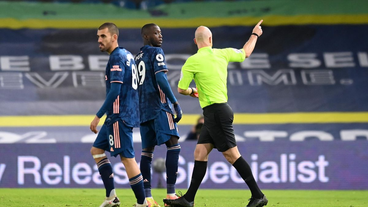 Nicolas Pepe of Arsenal(C) is shown a red card by Match Referee Anthony Taylor(R) during the Premier League match between Leeds United and Arsenal at Elland Road on November 22, 2020 in Leeds, England.