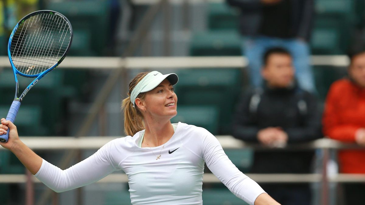 Maria Sharapova of Russia serves to Irina-Camelia Begu of Romania during their women's singles first round match at the WTA Tianjin Open tennis tournament in Tianjin on October 11, 2017.