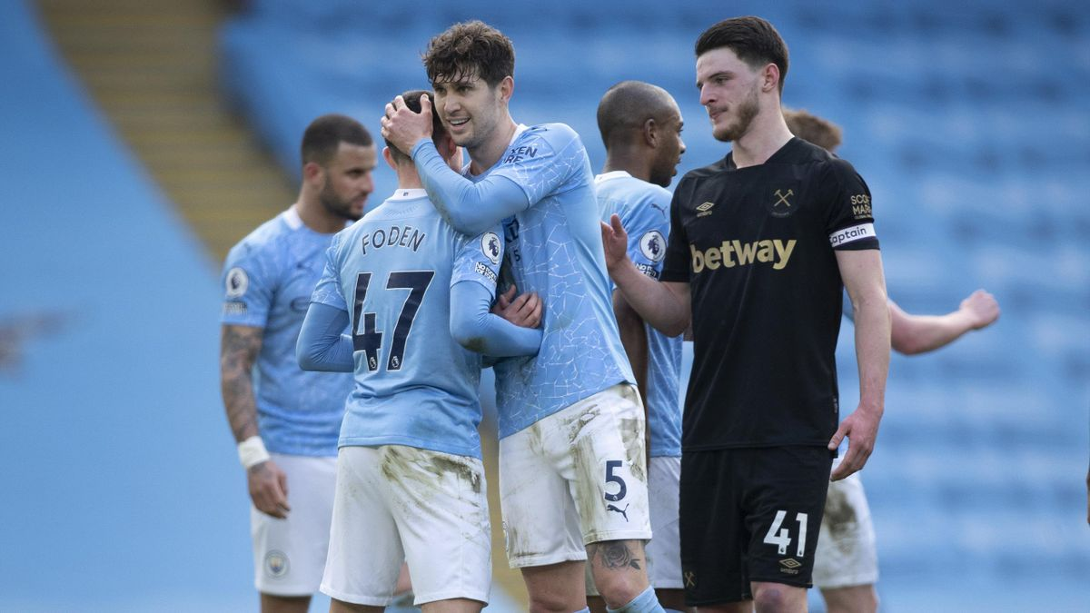 John Stones and Phil Foden of Manchester City greet each other at the final whistle whilst Declan Rice of West Ham United waits to shake hands during the Premier League match between Manchester City and West Ham United at Etihad Stadium on February 27, 20