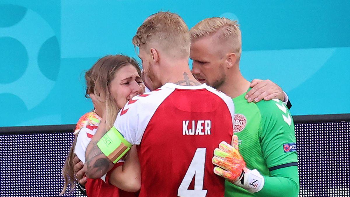 Denmark's goalkeeper Kasper Schmeichel (R) and Denmark's defender Simon Kjaer (C) comfort Sabrina Kvist Jensen, partner of Denmark's midfielder Christian Eriksenduring the UEFA EURO 2020 Group B football match between Denmark and Finland
