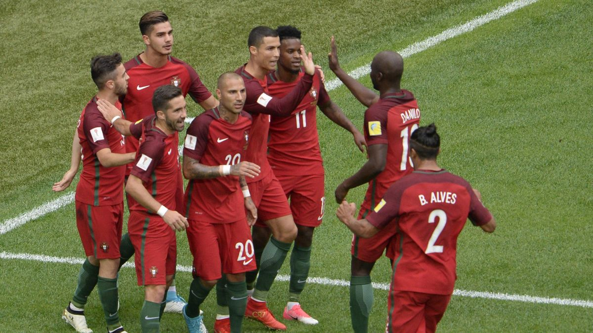 Portugal's forward Cristiano Ronaldo (C) celebrates with teammates after scoring a penalty
