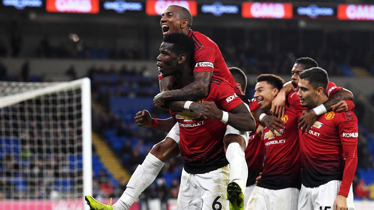Paul Pogba of Manchester United and Ashley Young of Manchester United celebrate as teammate Jesse Lingard scores their team's fifth goal during the Premier League match between Cardiff City and Manchester United.