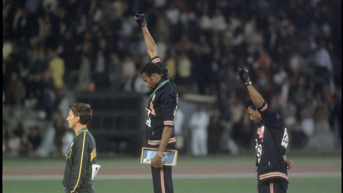 """Tommy Smith (307) (1st place) and John Carlos (259) (3rd place) of the US raise their fists in the """"Black Power Salute"""" during the playing of the national anthem at the Olympics in Mexico City"""