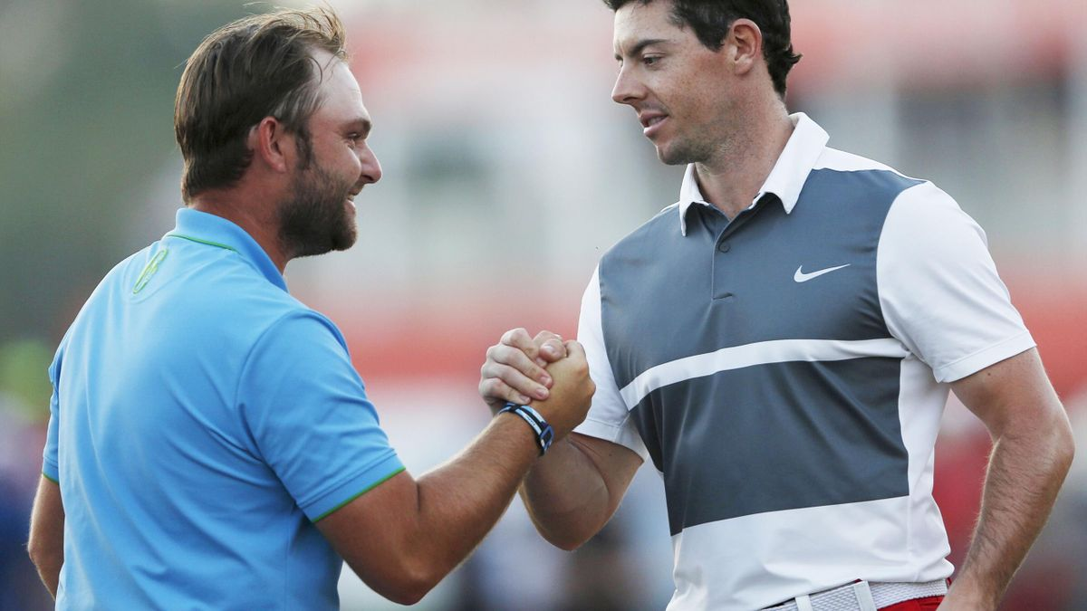 Andy Sullivan (L) of England clasps hands with Rory McIlroy of Northern Ireland at the end of their playing day on the ninth green during the Abu Dhabi Golf Championship January 23, 2016.