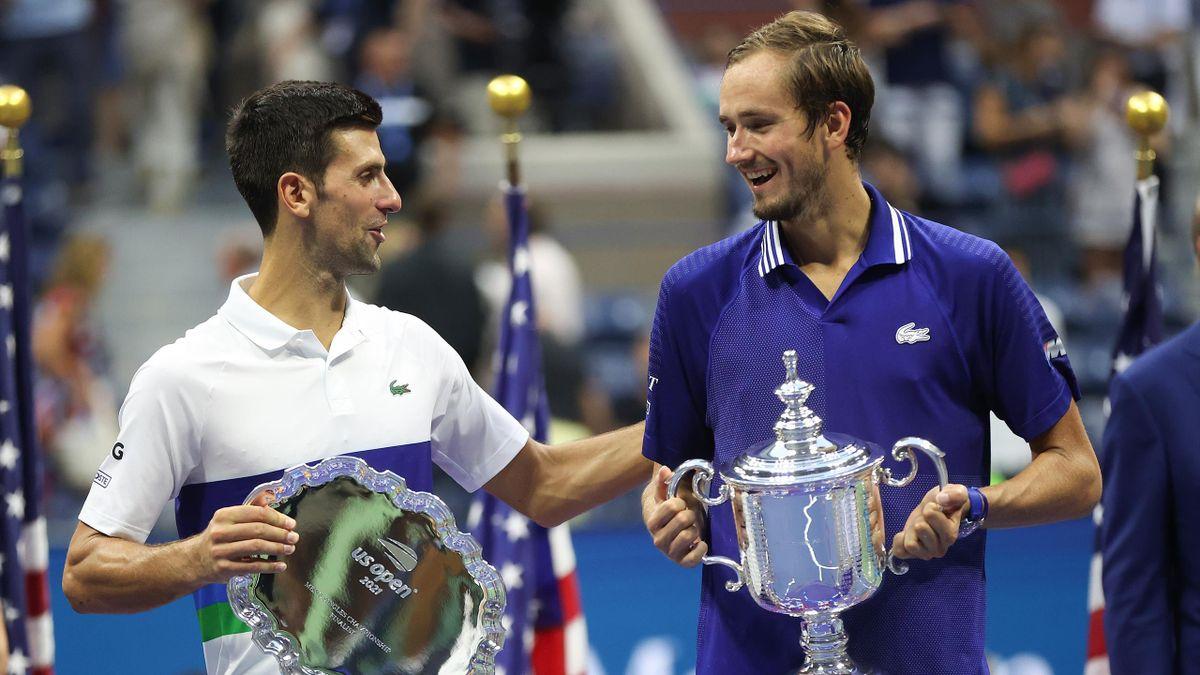 Novak Djokovic of Serbia holds the runner-up trophy alongside Daniil Medvedev of Russia