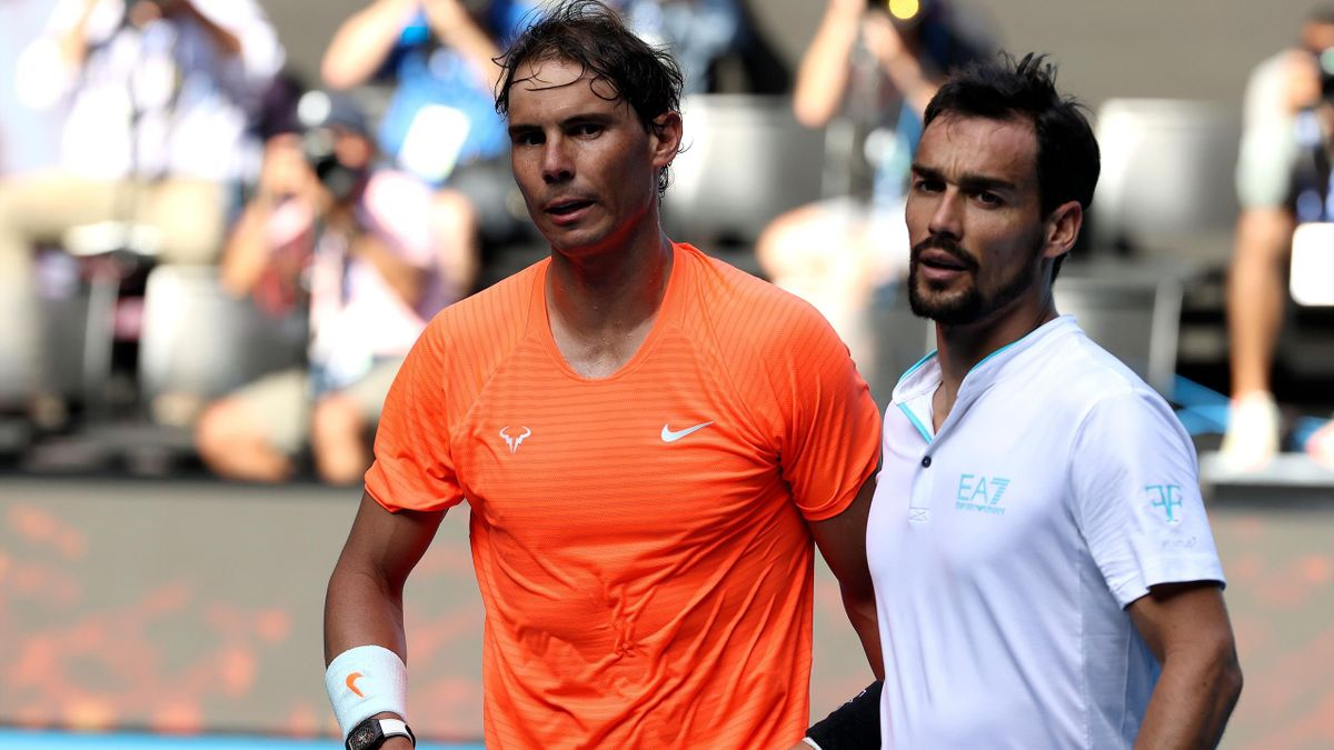 Spain's Rafael Nadal (L) and Italy's Fabio Fognini walk back to their seats after their men's singles match on day eight of the Australian Open tennis tournament in Melbourne on February 15, 2021.