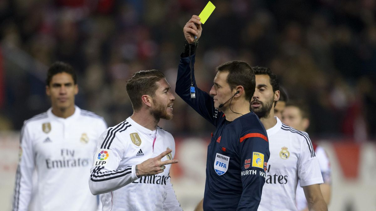 Real Madrid's defender Sergio Ramos (2ndL) is shown a yellow card during the Spanish Copa del Rey (King's Cup) round of 16 first leg football match Club Atletico de Madrid vs Real Madrid CF
