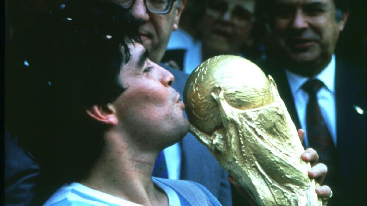 Diego Maradona kisses the World Cup trophy