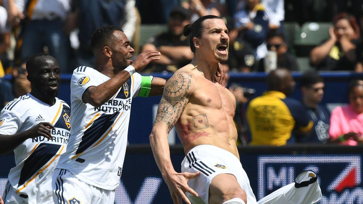 Zlatan Ibrahimovic from LA Galaxy (R) celebrates with teammates Emmanuel Boateng (L) and Ashley Cole (C)