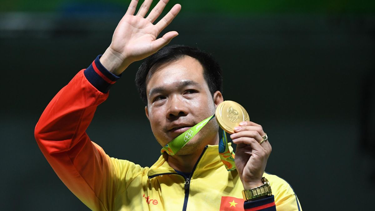 Vietnam's gold medallist Hoang Xuan Vinh poses on the podium during the medal ceremony for the men's 10m air pistol shooting