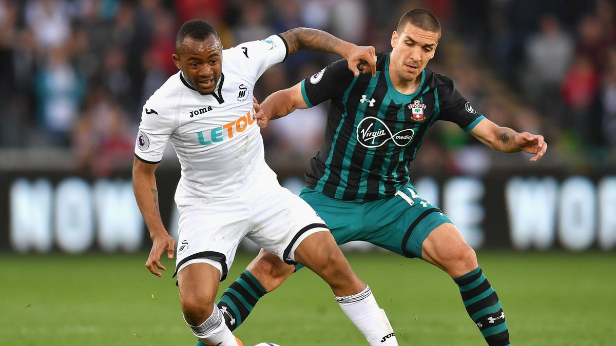 Jordan Ayew of Swansea City holds off Oriol Romeu of Southampton during the Premier League match between Swansea City and Southampton at Liberty Stadium on May 8, 2018.