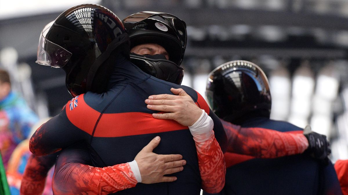 Great Britain-1 four-man bobsleigh pilot John James Jackson, pushman Stuart Benson, pushman Bruce Tasker and brakeman Joel Fearon hug each other after competing in the Bobsleigh Four-man Heat 4 and final run at the Sanki Sliding Center during the Sochi Wi