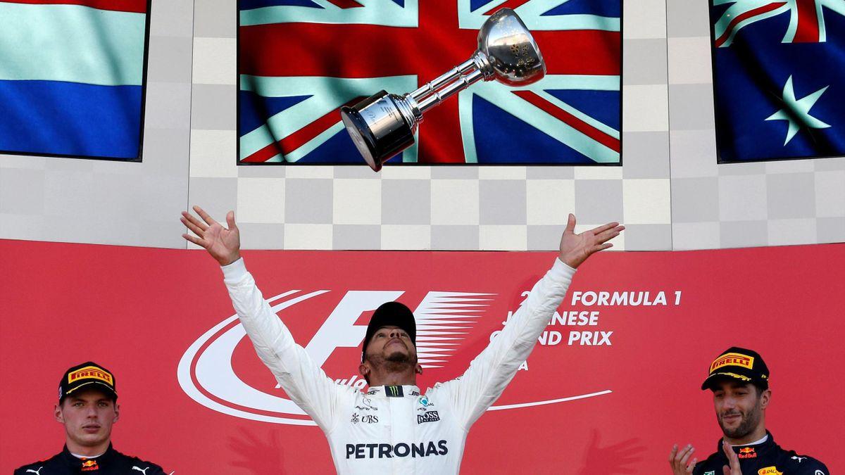 Mercedes' Lewis Hamilton of Britain celebrates winning the race next to Bull's Daniel Ricciardo of Australia and Max Verstappen of the Netherlands.