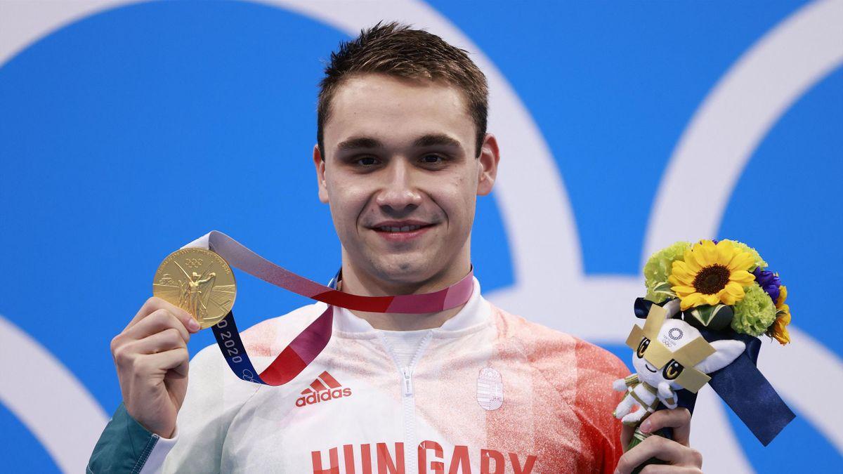 Az olimpiai bajnok Milák Kristóf egyik kezében az aranyéremmel, a másikban a virágcsokorral