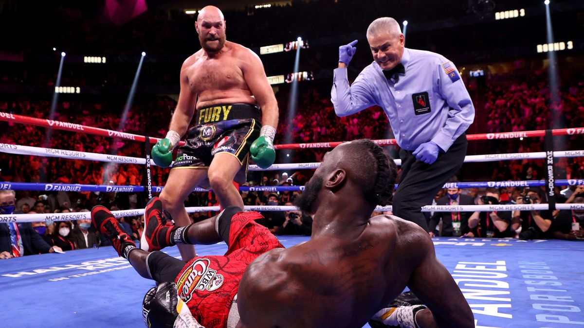 LAS VEGAS, NEVADA - OCTOBER 09: Tyson Fury (top) reacts after knocking down Deontay Wilder in the third round of their WBC Heavyweight Championship title fight at T-Mobile Arena on October 09, 2021 in Las Vegas, Nevada.