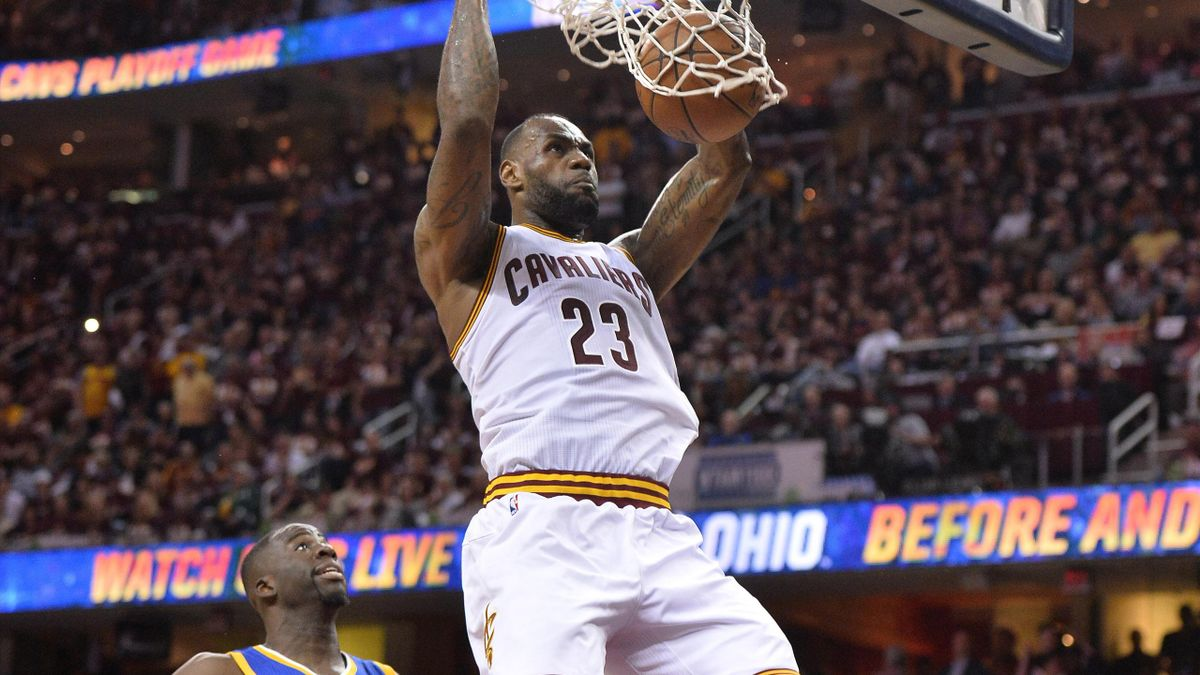 Cleveland Cavaliers forward LeBron James (23) dunks the ball in front of Golden State Warriors forward Draymond Green (23) during the four quarter in game three of the NBA Finals at Quicken Loans Arena.