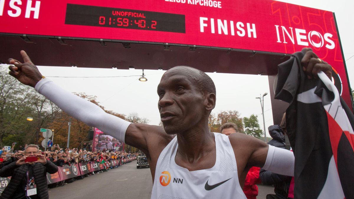 Kenya's Eliud Kipchoge (white jersey) celebrates after busting the mythical two-hour barrier for the marathon on October 12 2019 in Vienna