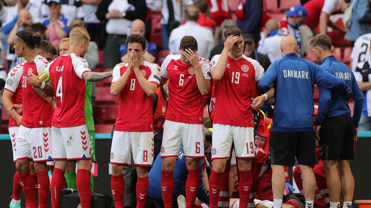 TOPSHOT - Players gather as paramedics attend to Denmark's midfielder Christian Eriksen (not seen) during the UEFA EURO 2020 Group B football match between Denmark and Finland at the Parken Stadium in Copenhagen on June 12, 2021.